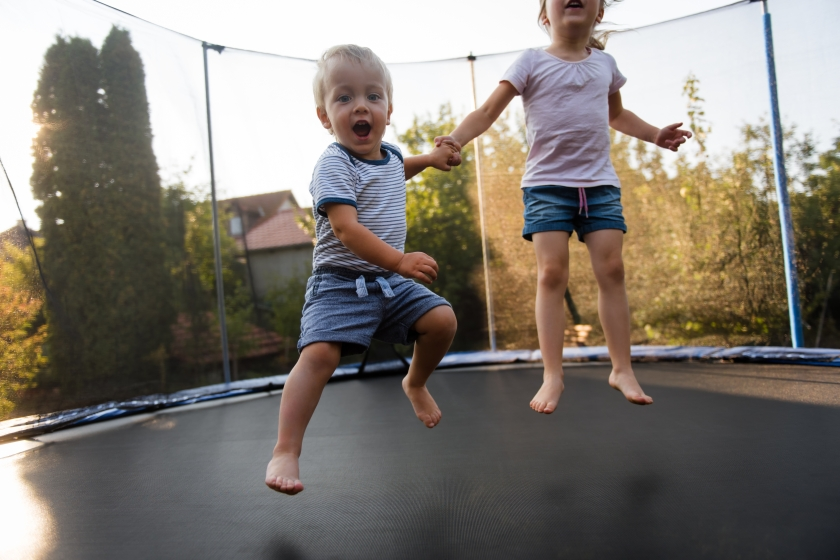 Siblings,Jump,On,Trampoline,While,Holding,Hands